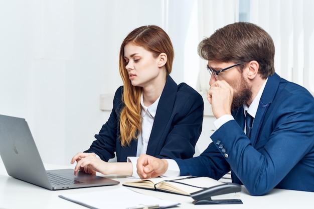 Koledzy rozmawiający w biurze przed technologią laptopa