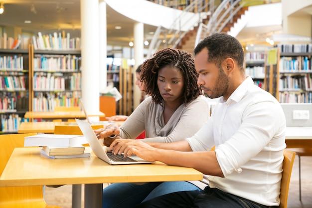 Koledzy siedzący przy bibliotece i korzystający z laptopa