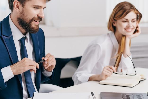 Koledzy siedzący przy stole przed laptopem team technology
