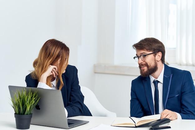 Koledzy siedzący przy stole przed laptopem w technologii biurowej