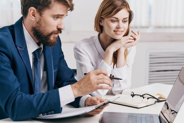 Koledzy siedzący przy stole przed technologią profesjonalistów od laptopów