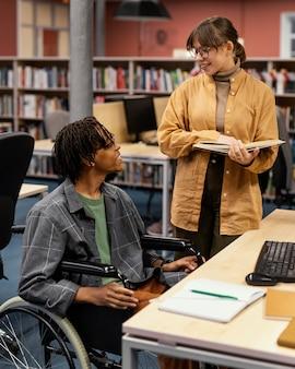 Koledzy studiujący w bibliotece uniwersyteckiej
