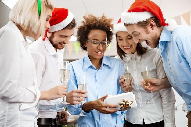 Koledzy świętuje przyjęcie gwiazdkowe w biurze ono uśmiecha się dawać teraźniejszości.