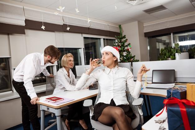 Koledzy świętuje przyjęcie gwiazdkowe w biurze pije szampana ono uśmiecha się.