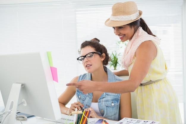 Koledzy używający komputera i wskazujący ekran
