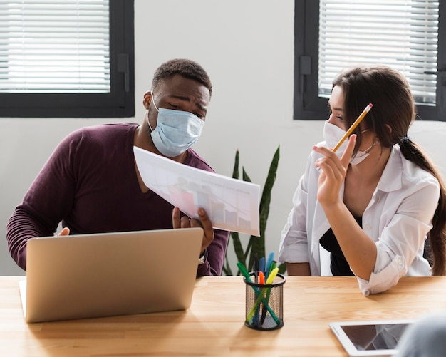 Koledzy w biurze podczas pandemii w maskach medycznych