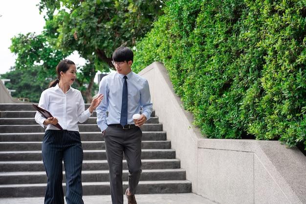 Koledzy w biznesie omawiają kwestie związane z pracą na zewnątrz w pobliżu biurowca, rozmawiają ze sobą na zewnątrz.