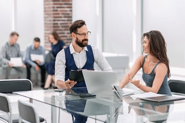 Koledzy w biznesie rozmawiają o sprawach biznesowych siedząc przy biurku