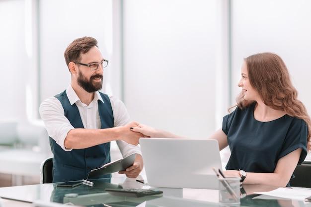 Koledzy w biznesie, ściskając ręce na biurku