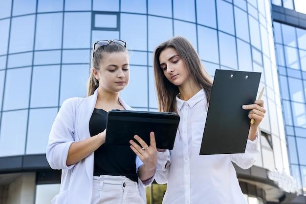 Koledzy w biznesie stoją przed dużym centrum biurowym z tabletem i schowkiem