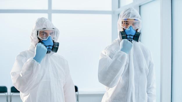 Koledzy w kombinezonach chroniących przed zagrożeniem biologicznym stoją w laboratorium