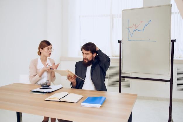 Koledzy w pracy w biurze przy biurku komunikacja dyskusja