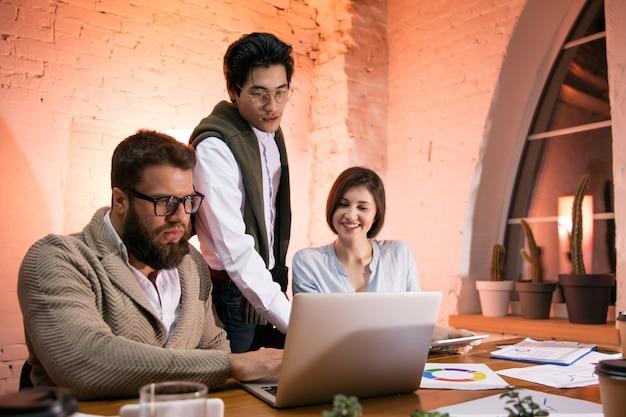 Koledzy współpracujący w nowoczesnym biurze przy użyciu urządzeń i gadżetów podczas kreatywnego spotkania. dyskusja, podejmowanie decyzji, rutynowe zadania, projekty. udana korporacyjna praca zespołowa.