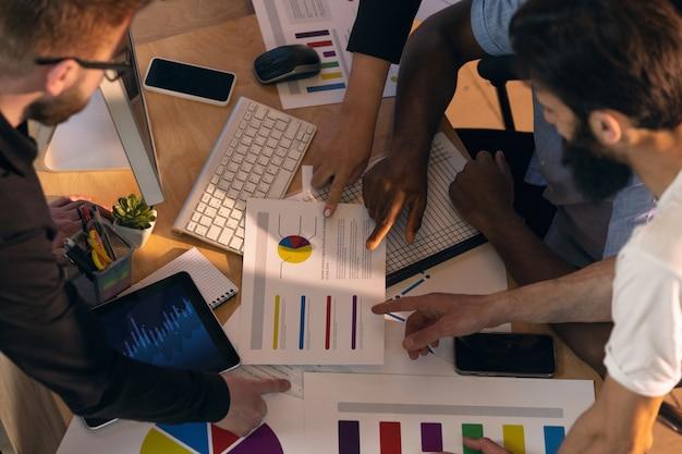 Koledzy współpracujący w nowoczesnym biurze przy użyciu urządzeń i gadżetów podczas kreatywnego spotkania