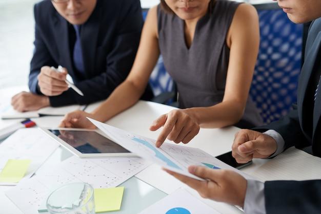 Koledzy wykonujący pracę zespołową, siedząc przy stole biura