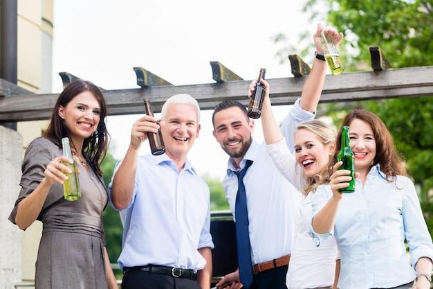 Koledzy z biura piją piwo po pracy na tarasie świętując