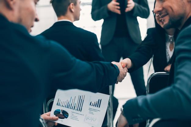 Koledzy z biznesu ściskają sobie dłonie podczas warsztatów. pomysł na biznes