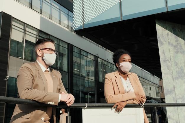 Koledzy z biznesu w maskach ochronnych stojący na zewnątrz w pobliżu biurowca podczas pandemii
