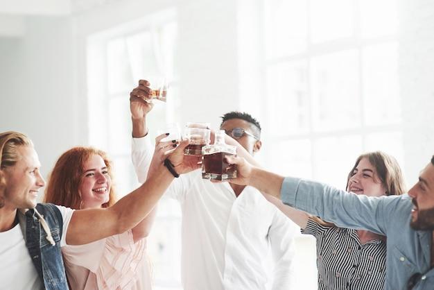Koledzy z drużyny pijący whisky i śmiejący się z powodu udanej transakcji