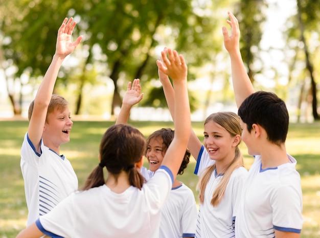 Koledzy z drużyny są szczęśliwi po wygraniu meczu piłki nożnej