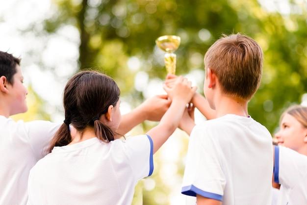Koledzy z drużyny trzymający razem złote trofeum