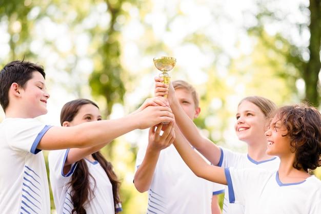 Koledzy z drużyny trzymający złote trofeum