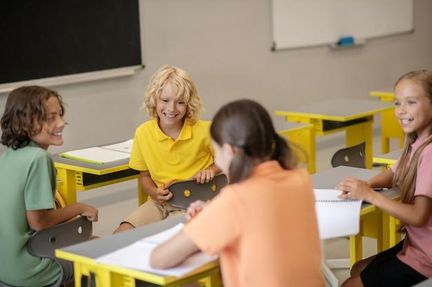 Koledzy z klasy. dzieci siedzą przy ławkach w klasie i rozmawiają