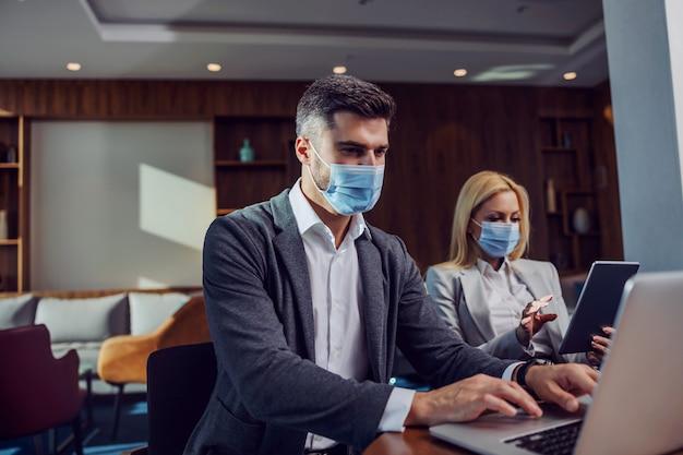 Koledzy z maskami na twarzach siedzący w przestrzeni biznesowej na oficjalnym spotkaniu biznesowym. mężczyzna za pomocą laptopa