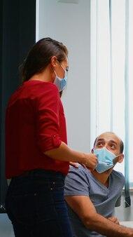 Koledzy z maskami rozmawiają o grafice siedząc w nowym, normalnym pokoju biurowym. współpracownicy rozmawiają w pracy, wskazując na pulpit, szanując dystans społeczny przed wirusem covid za pomocą pleksi.