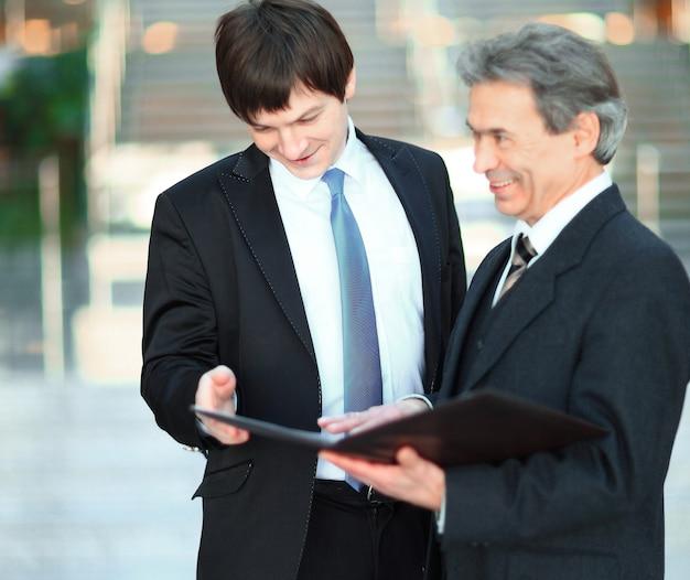 Koledzy z pracy omawiają dokumenty biznesowe stojące w biurze.zdjęcie z miejscem na kopię