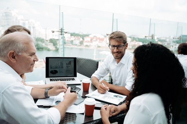 Koledzy z pracy omawiają dokumenty finansowe z bliska