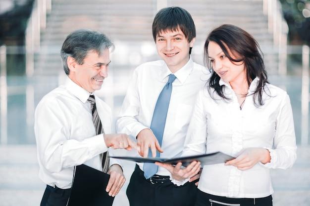 Koledzy z pracy omawiają dokumenty robocze stojąc w nowoczesnym biurze