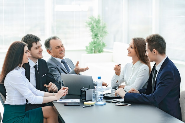 Koledzy z pracy rozmawiają przy biurku w biurze. koncepcja pracy zespołowej