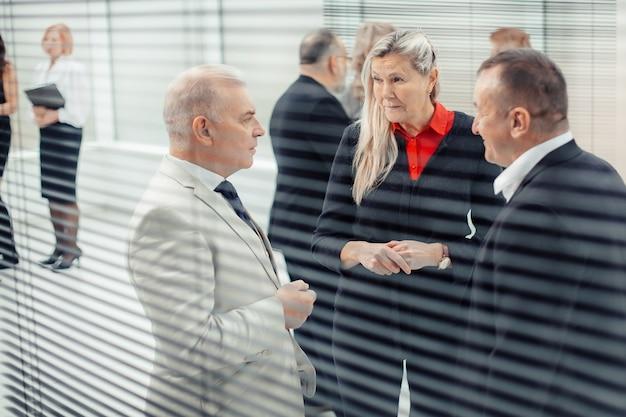 Koledzy z pracy rozmawiają stojąc w biurze
