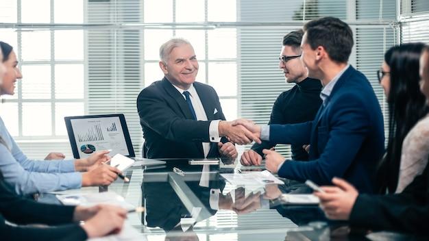 Koledzy z pracy uścisk dłoni podczas spotkania w pracy. pojęcie pracy zespołowej