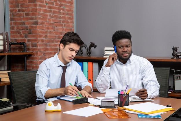 Koledzy z procesu pracy zespołu z widokiem z przodu prowadzący negocjacje biznesowe w nowoczesnym biurze