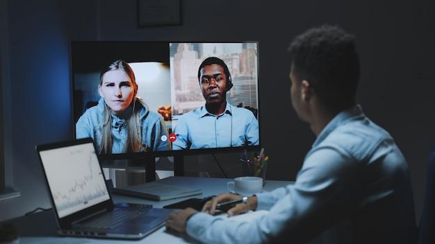 Koledzy z różnych ras pracujący w domu na kwarantannie, wykonując wspólną rozmowę wideo na dużym monitorze