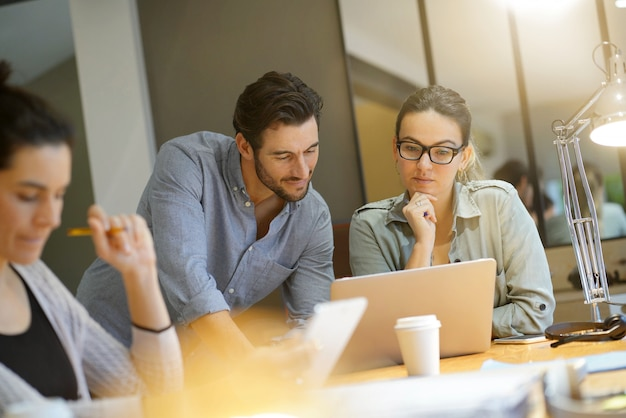 Koledzy z warsztatów omawiający pomysły biznesowe w nowoczesnej przestrzeni roboczej