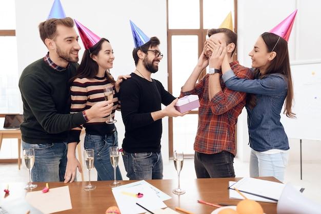 Koledzy zaskakują innego pracownika firmy.