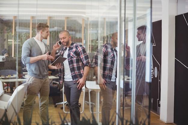 Kolega dyskutuje podczas gdy biznesmen opowiada na telefonie