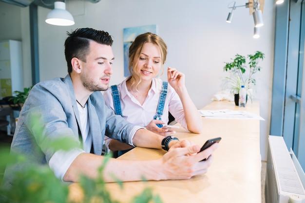 Kolega patrzeje smartphone w biurze