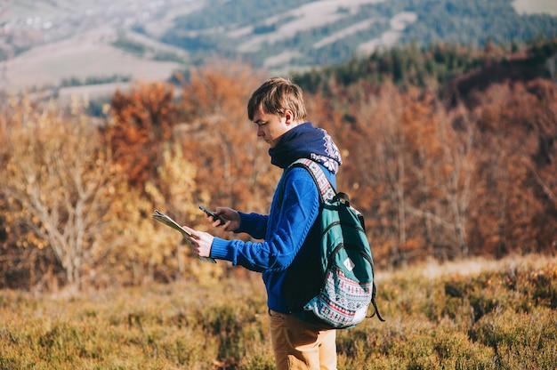 Kolega turysta z mapy w ręku i telefonu. jesienne góry