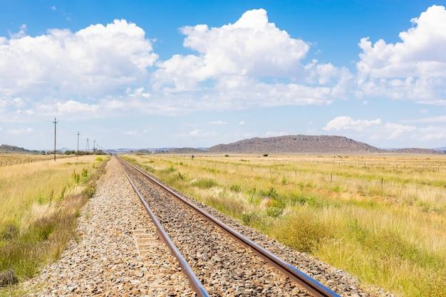 Kolej na środku pola suchej trawy pod zachmurzonym błękitnym niebem