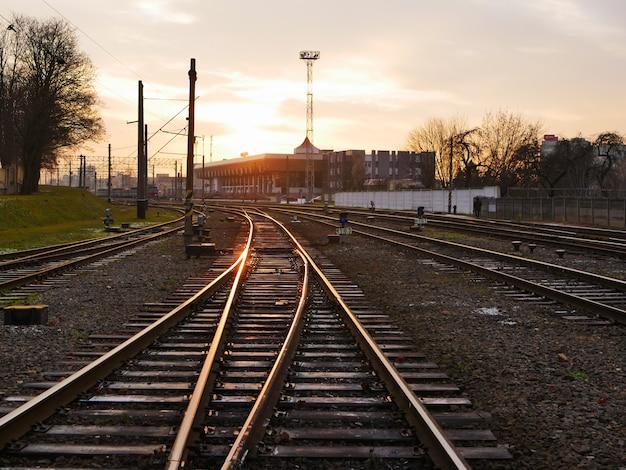Kolej o zachodzie słońca. stacja kolejowa o zachodzie słońca. krajobraz przemysłowy z koleją. węzeł kolejowy przemysł ciężki. wieczór w drodze