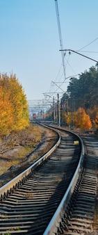 Kolej przechodzi przez piękny jesienny las porośnięty kolorowymi drzewami.