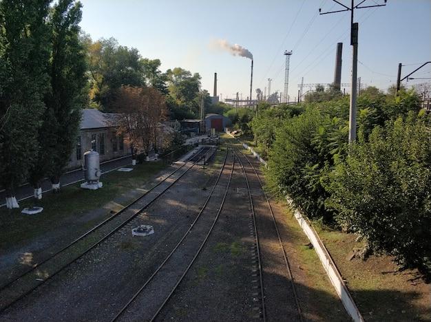Kolej żelazna. puste szyny z dymnymi kominami rośliny