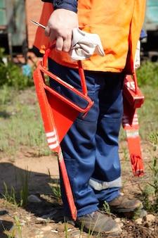Kolejarz w pomarańczowej kamizelce sygnalizacyjnej i broni trzyma w ręku czerwoną szczękę hamulcową