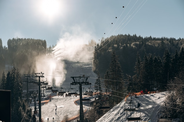 Kolejka linowa w górach ze słoneczną zimową pogodą w tle. kolejka linowa z kabinami, kolejką linową, kolejką linową w ośrodku narciarskim lub snowboardowym. zimowa sceneria z koncepcją lasu