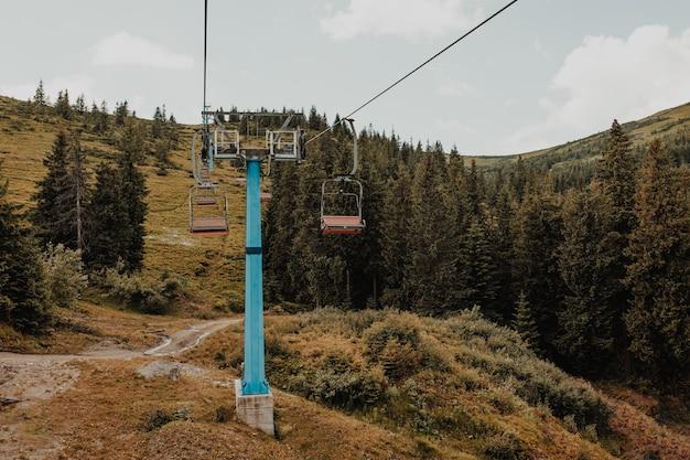 Kolejka linowa w ruchu na szczycie góry przed zachmurzonym błękitnym niebem, sportem i aktywnym życiem