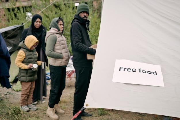 Kolejka migrantów stojących przed namiotem wolontariatu